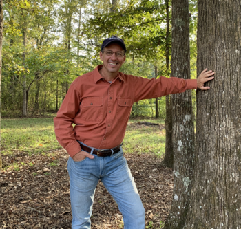 Consulting Forester Tom Manual leaning against the trunk of a tree